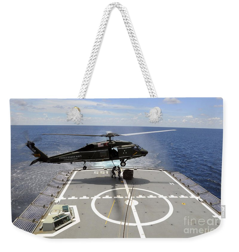 Military Weekender Tote Bag featuring the photograph An Sh-60f Sea Hawk Helicopter Lowers by Stocktrek Images