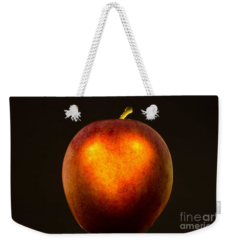 Apple Weekender Tote Bag featuring the photograph Apple With A Illuminated Heart by Mats Silvan