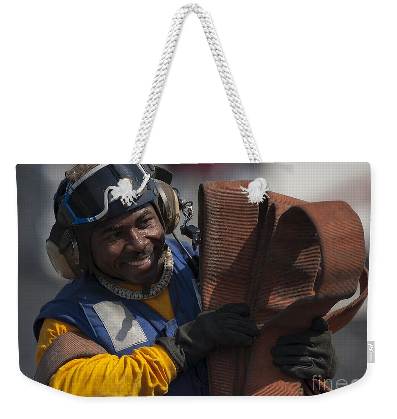 Military Weekender Tote Bag featuring the photograph Aviation Boatswains Mate Carrying by Stocktrek Images