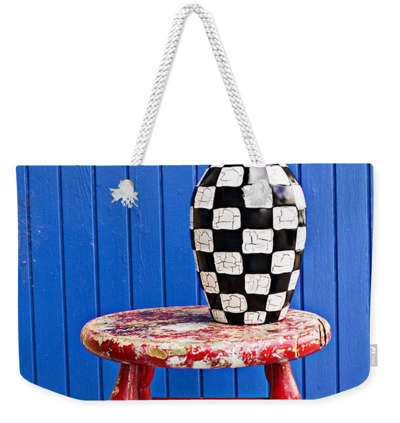 Vase Weekender Tote Bag featuring the photograph Blach And White Vase On Stool Against Blue Wall by Garry Gay
