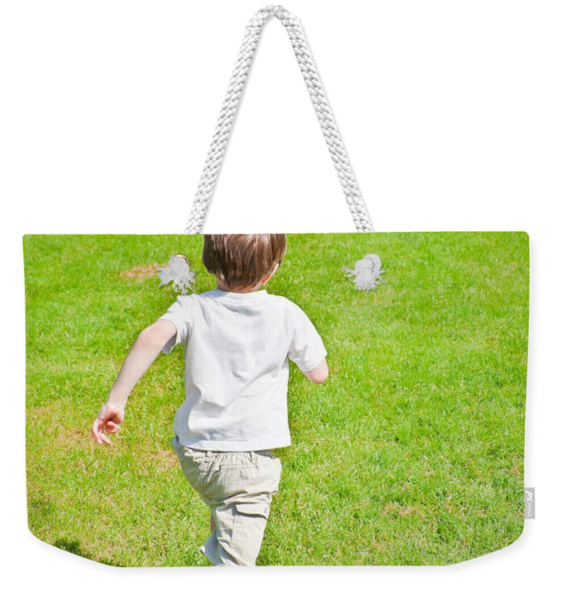 Activity Weekender Tote Bag featuring the photograph Boy Running by Tom Gowanlock