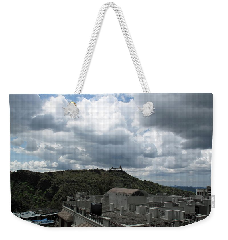 Jammu Weekender Tote Bag featuring the photograph Buildings Cover The Lower Section Of A Hill That Has A Temple At The Top With Clouds Covering The Sk by Ashish Agarwal