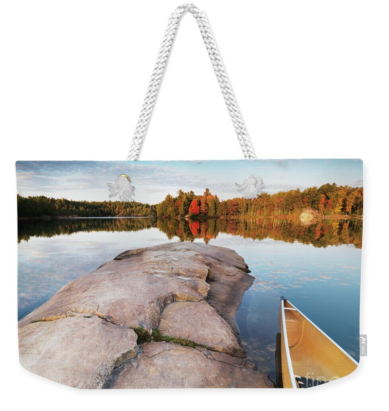 Canoe Weekender Tote Bag featuring the photograph Canoe At A Rocky Shore Autumn Nature Scenery by Oleksiy Maksymenko