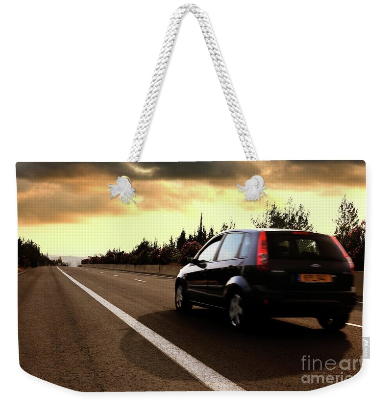 Car Weekender Tote Bag featuring the photograph Car On The Road During Sunset by Oleksiy Maksymenko