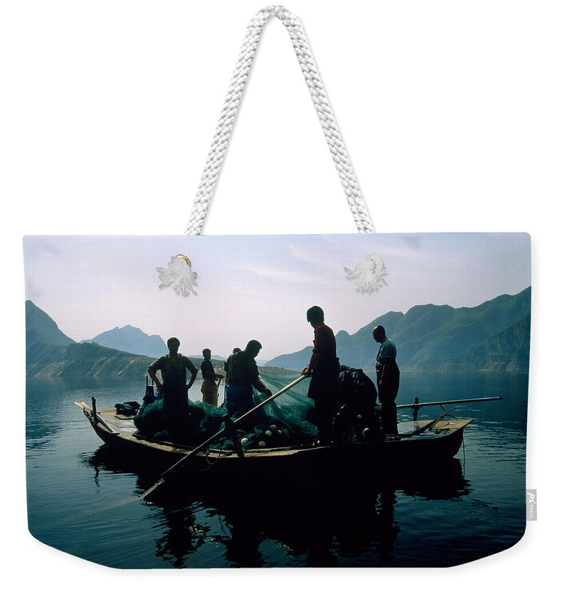 Fishing Weekender Tote Bag featuring the photograph Carp Fishermen In Lake Formed By A Dam by Michael S. Yamashita