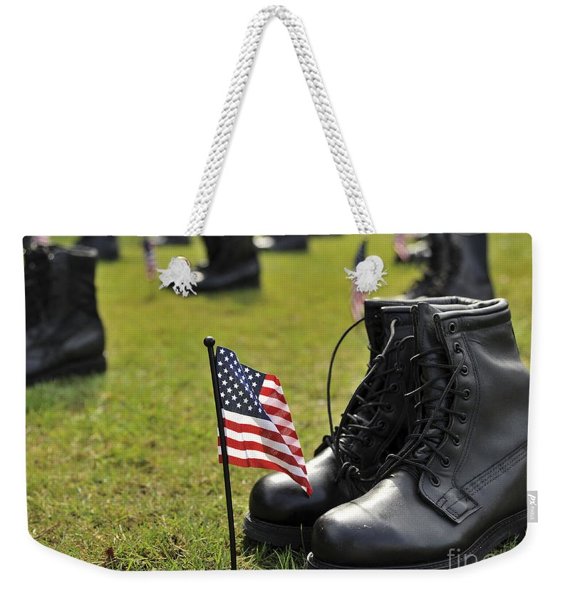 Iconic Weekender Tote Bag featuring the photograph Combat Boots Are Placed In Formation by Stocktrek Images