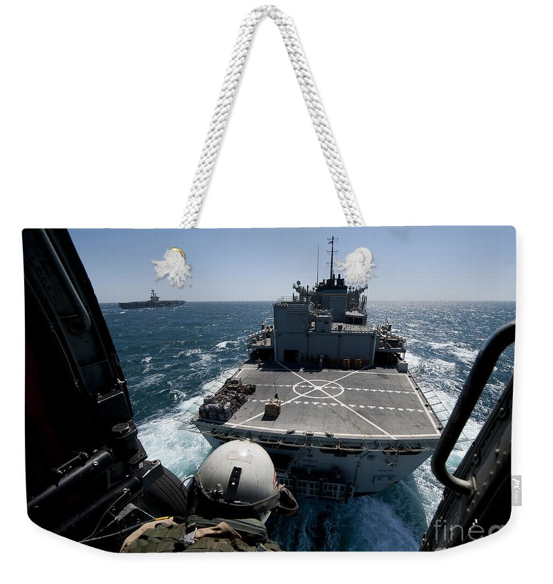 Military Weekender Tote Bag featuring the photograph Crewman Guides The Pilots Of An Hh-60h by Stocktrek Images