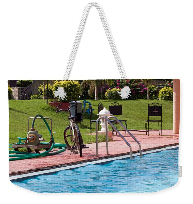 Cycle Weekender Tote Bag featuring the photograph Cycle Near A Swimming Pool And Greenery by Ashish Agarwal