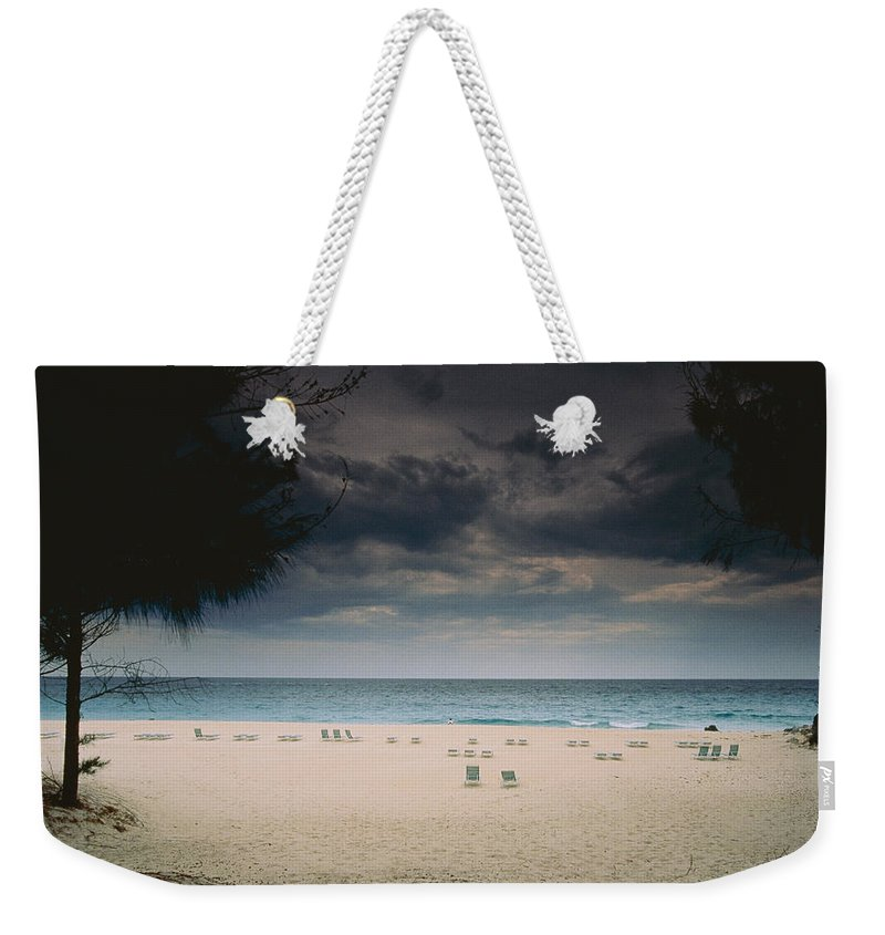 Bermuda Island Weekender Tote Bag featuring the photograph Empty Lounge Chairs Litter A Quiet by Todd Gipstein