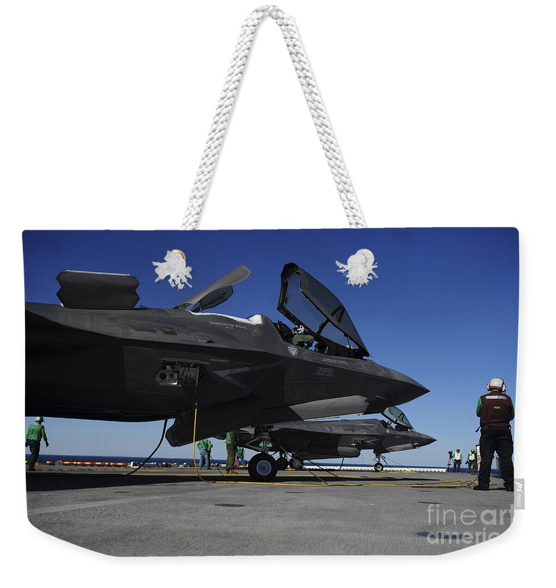 Aerospace Weekender Tote Bag featuring the photograph F-35b Lightning II Variants Are Secured by Stocktrek Images