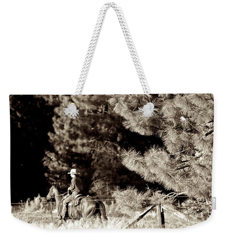 Cowboy Weekender Tote Bag featuring the photograph Fence Checkin' by Eric Tressler