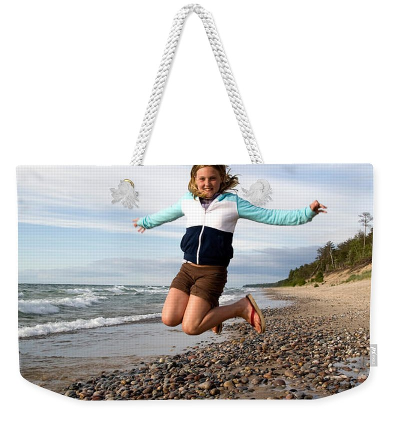Jump Weekender Tote Bag featuring the photograph Girl Jumping At Lake Superior Shore by Ted Kinsman