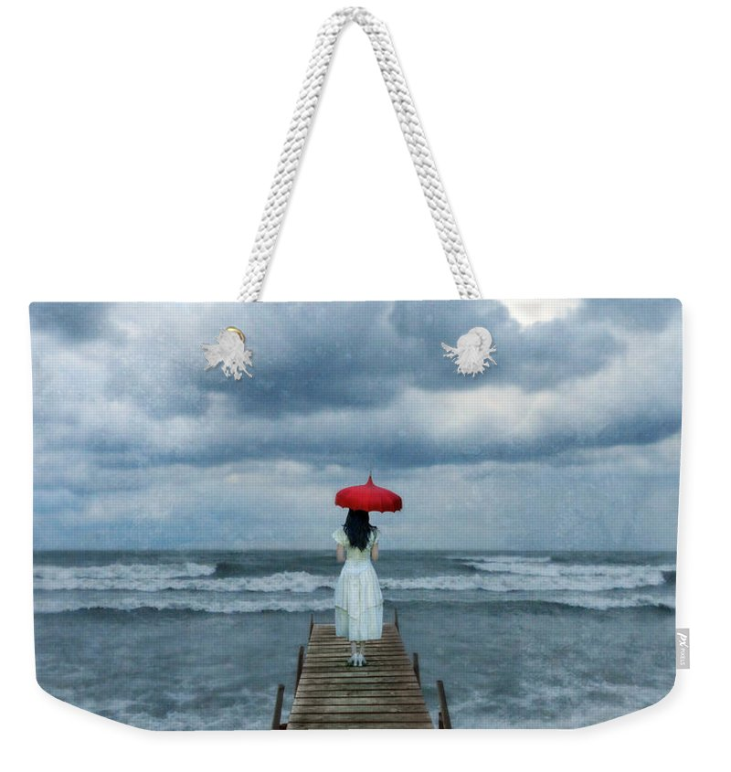 Young Weekender Tote Bag featuring the photograph Lady On Dock In Storm by Jill Battaglia