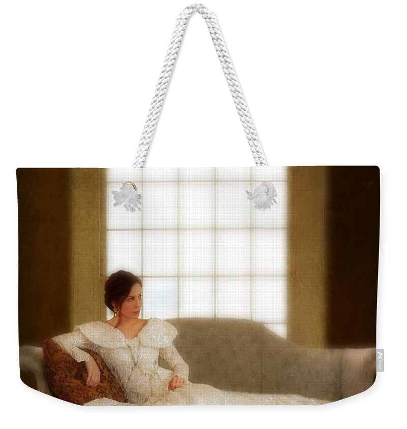 Beautiful Weekender Tote Bag featuring the photograph Lady Sitting On Sofa By Window by Jill Battaglia