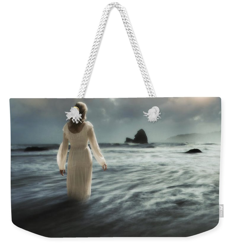 Walking Weekender Tote Bag featuring the photograph Lady Wading Into The Sea In The Early Morning by Jill Battaglia