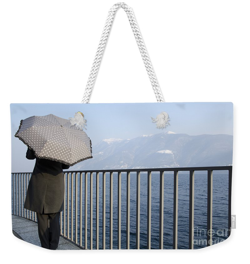 Woman Weekender Tote Bag featuring the photograph Lakefront With A Umbrella by Mats Silvan