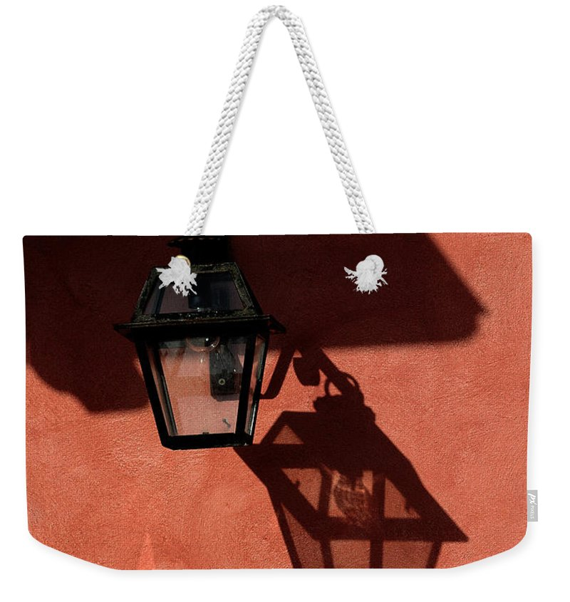 Lamp Weekender Tote Bag featuring the photograph Lamp On Peach Wall by Mike Nellums