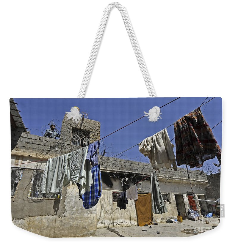 Operation Enduring Freedom Weekender Tote Bag featuring the photograph Laundry Hangs In The Courtyard by Stocktrek Images