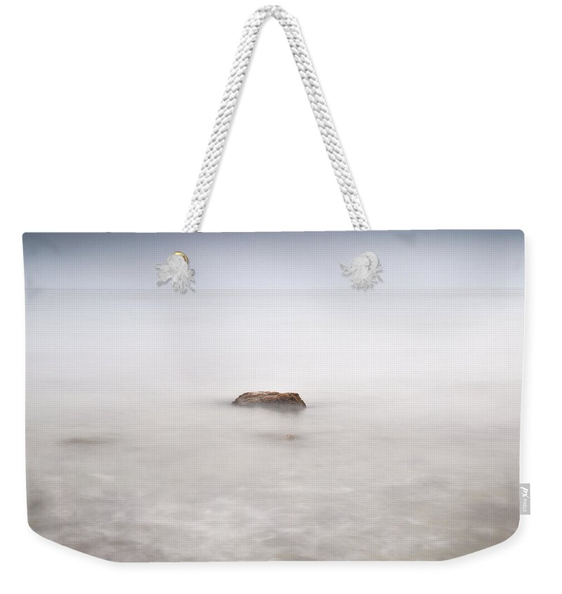 Seascape Weekender Tote Bag featuring the photograph Lonely Rock At The Silver Sea by Guido Montanes Castillo