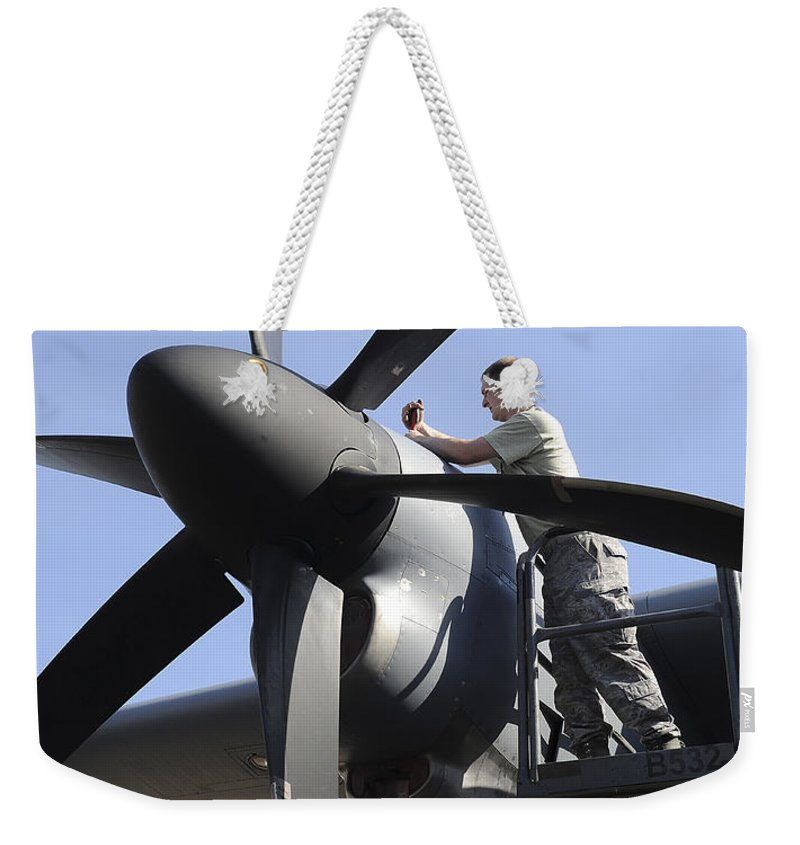 Military Weekender Tote Bag featuring the photograph Mechanic Finishes Moving An Engine by Stocktrek Images
