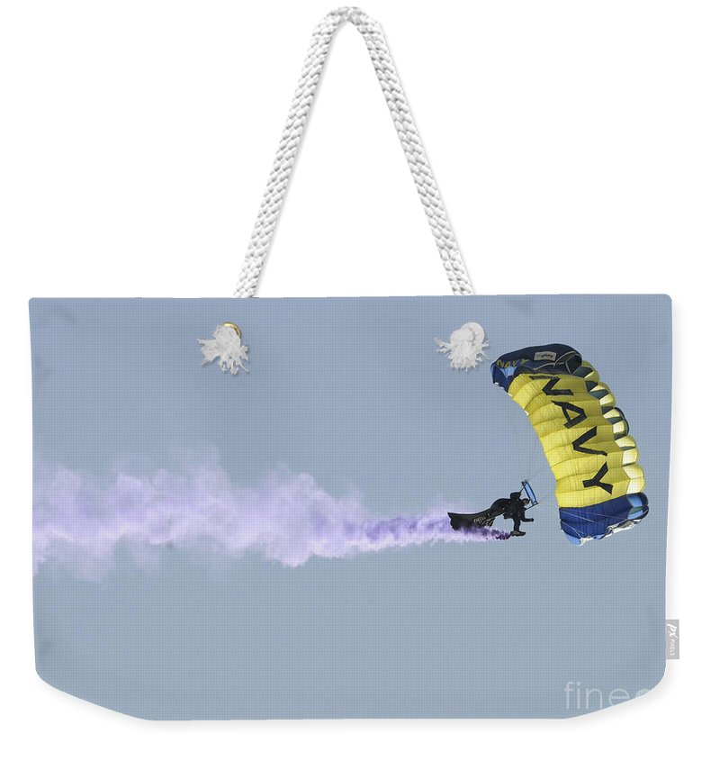 Leap Frogs Weekender Tote Bag featuring the photograph Member Of The U.s. Navy Parachute by Stocktrek Images