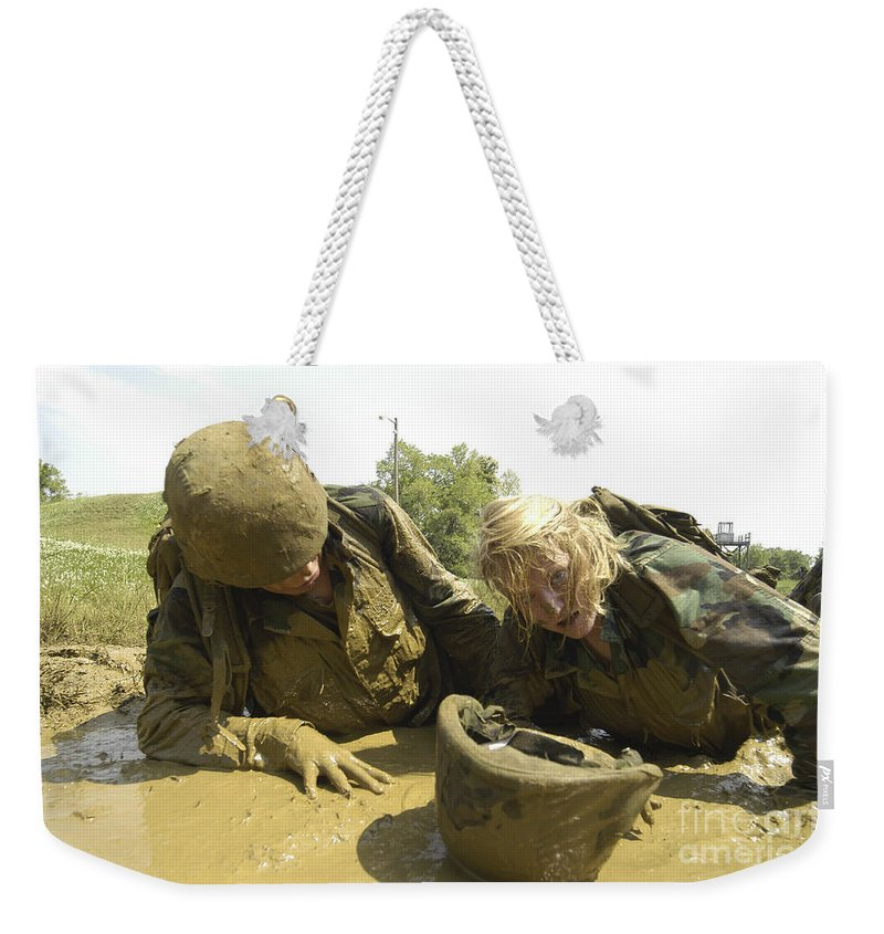 Navy Weekender Tote Bag featuring the photograph Midshipmen Maneuver Through A Mud Pit by Stocktrek Images