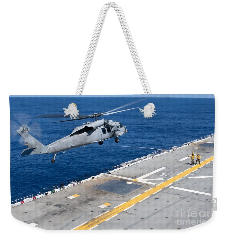 Us Navy Weekender Tote Bag featuring the photograph N Mh-60s Sea Hawk Helicopter Lifts by Stocktrek Images