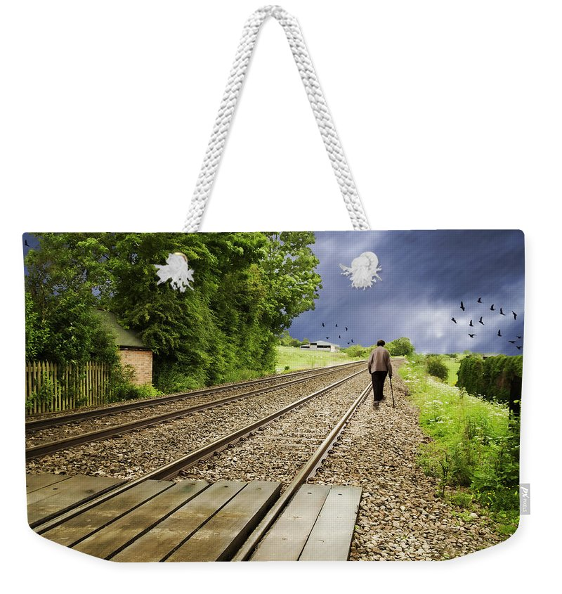 Old Weekender Tote Bag featuring the photograph Old Man Walks Along Train Tracks by Amanda Elwell