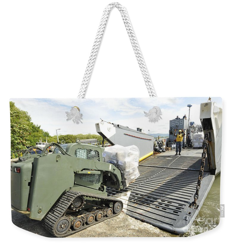 Colombia Weekender Tote Bag featuring the photograph Pallets Of Donated Goods Are Removed by Stocktrek Images