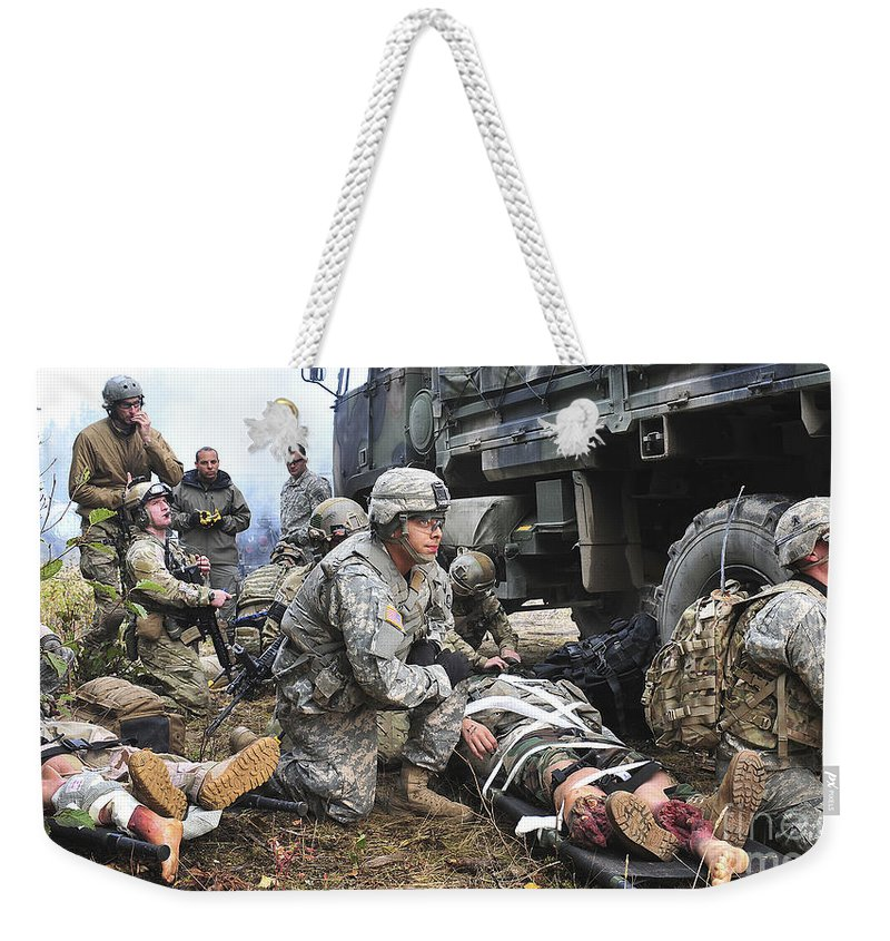 Pararescuemen Weekender Tote Bag featuring the photograph Pararescuemen Prepare To Transport by Stocktrek Images