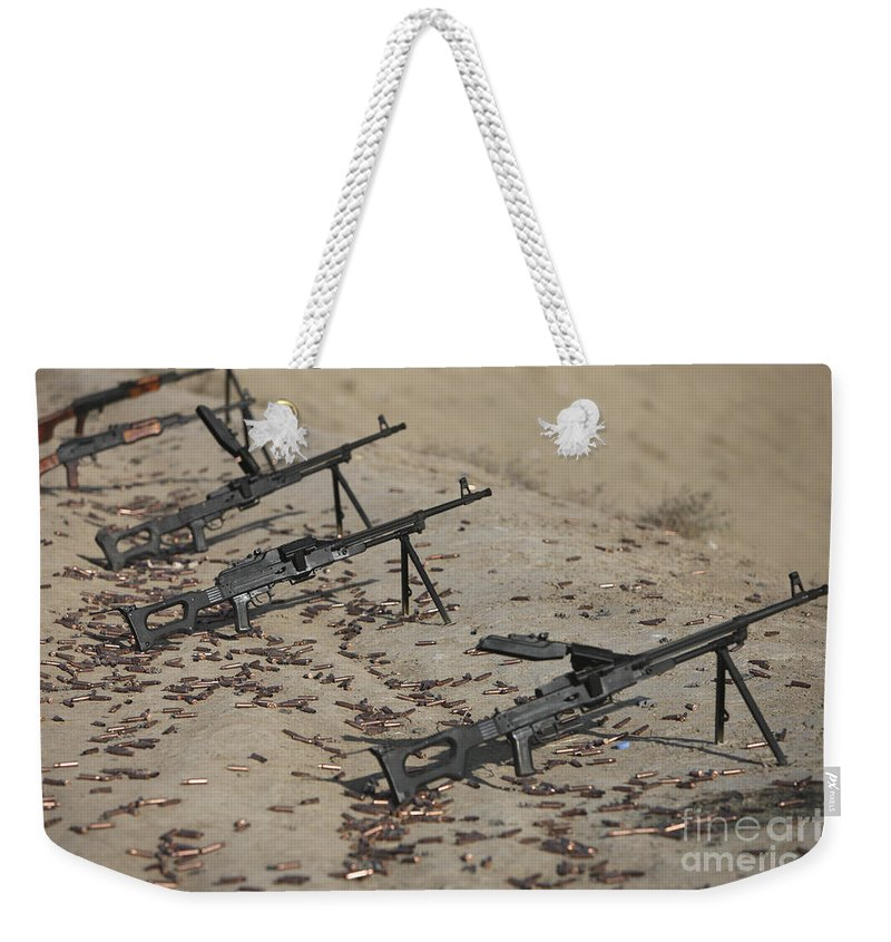 Kunduz Weekender Tote Bag featuring the photograph Pk Machine Guns And Spent Cartridges by Terry Moore