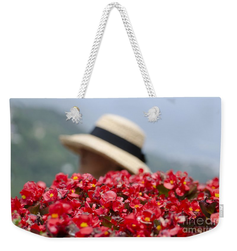 Red Weekender Tote Bag featuring the photograph Red Flowers And Straw Hat by Mats Silvan