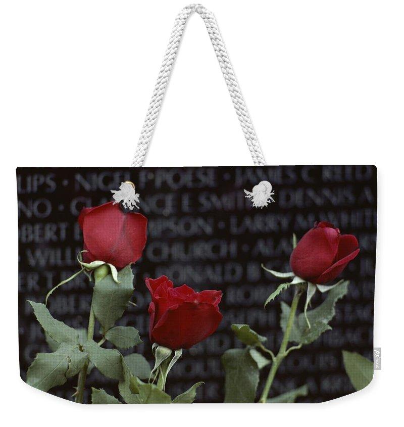 North America Weekender Tote Bag featuring the photograph Roses Glow Against The Black Granite by Karen Kasmauski