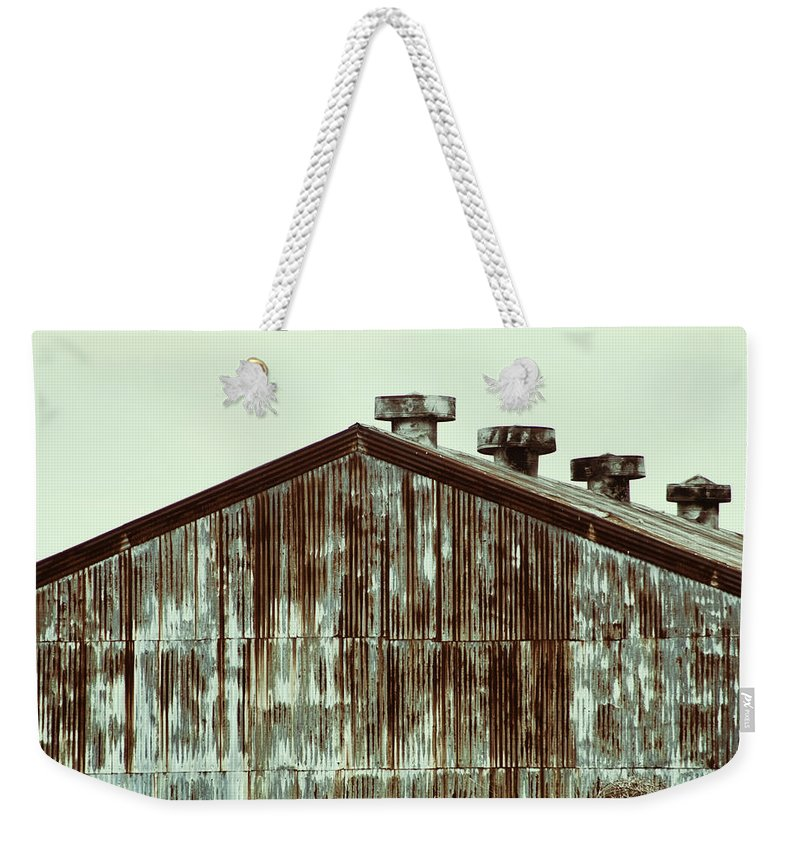 Tin Weekender Tote Bag featuring the photograph Rusty Tin Factory Building by Kathy Clark