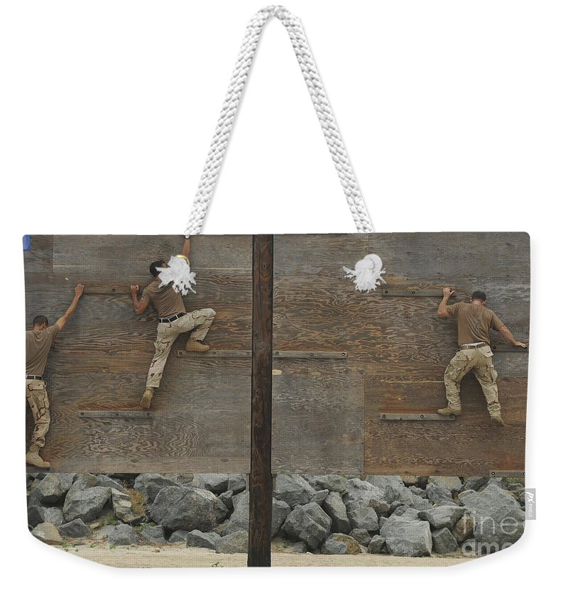 Obstacle Course Weekender Tote Bag featuring the photograph Sailors Crawl Across Narrow Planks by Stocktrek Images