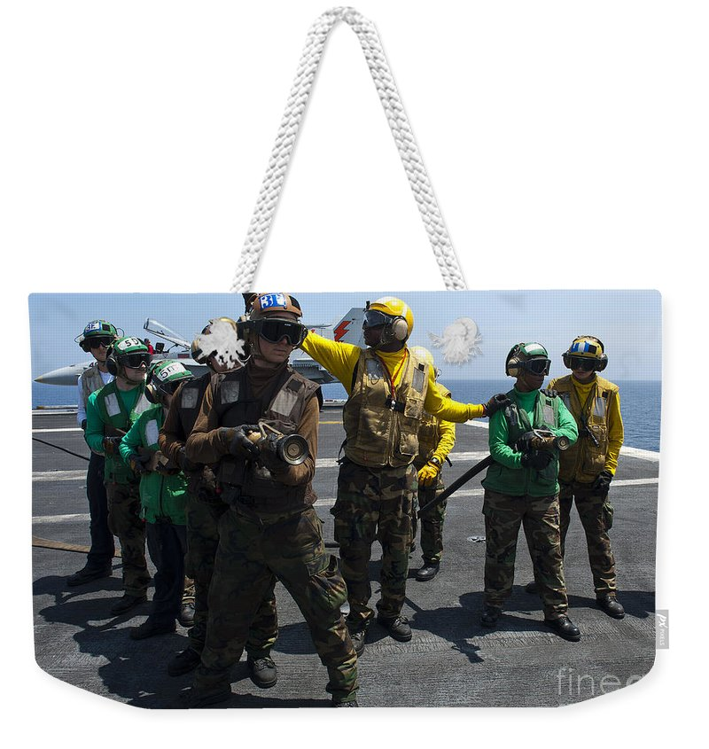 Operation Enduring Freedom Weekender Tote Bag featuring the photograph Sailors Fight A Simulated Fire Drill by Stocktrek Images
