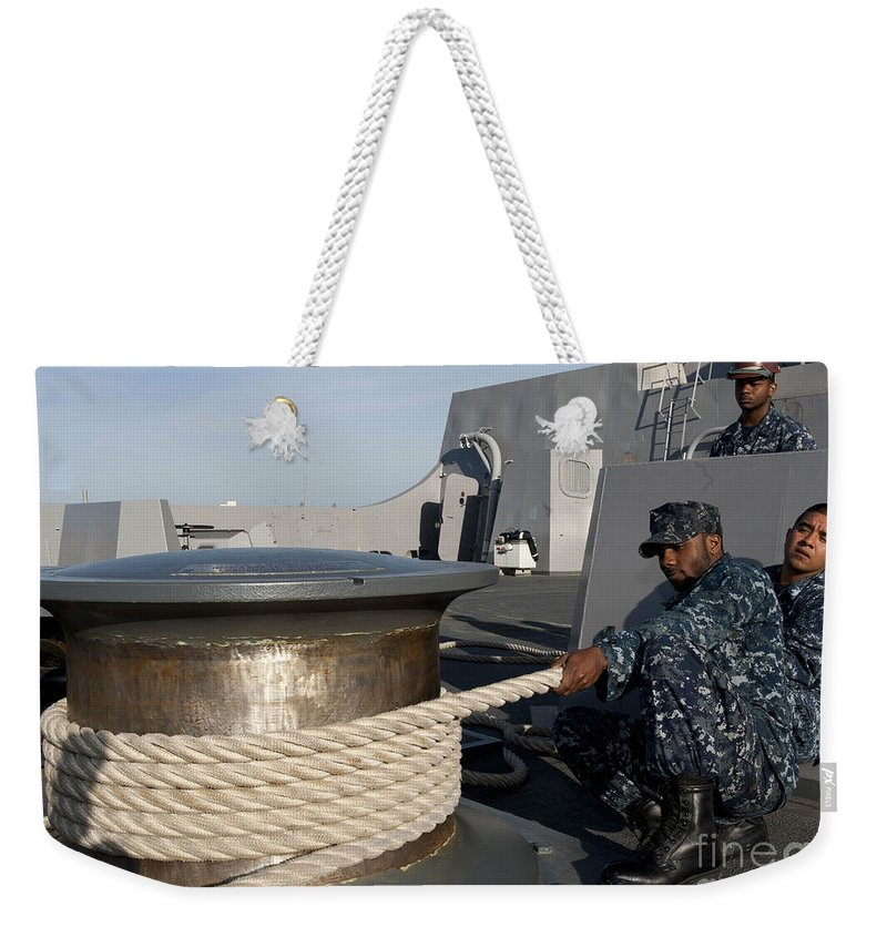 Military Weekender Tote Bag featuring the photograph Sailors Handle Mooring Lines Aboard Uss by Stocktrek Images