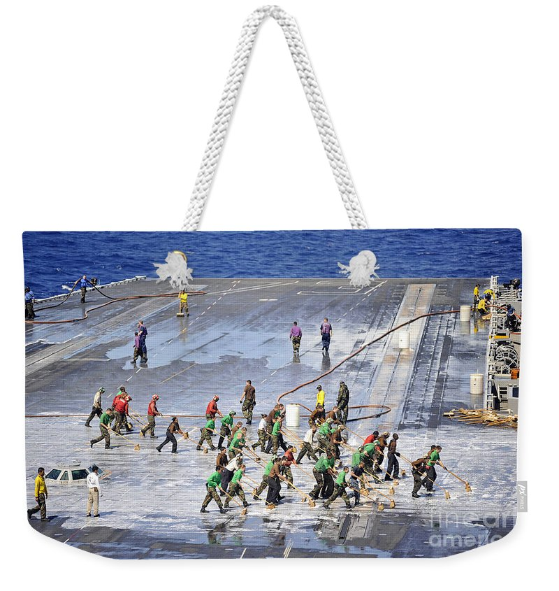 Pacific Ocean Weekender Tote Bag featuring the photograph Sailors Perform A Flight Deck Wash by Stocktrek Images