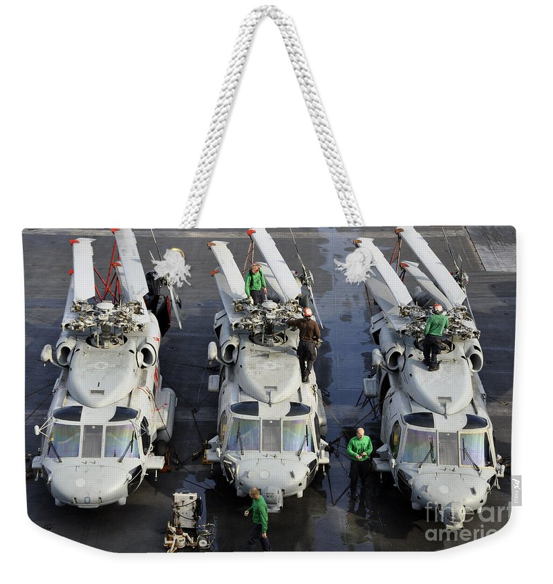 Aircraft Carrier Weekender Tote Bag featuring the photograph Sailors Perform Maintenance On Mh-60s by Stocktrek Images
