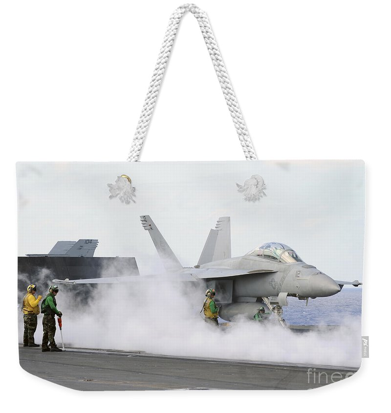 Uss George Washington Weekender Tote Bag featuring the photograph Sailors Prepare An Fa-18f Super Hornet by Stocktrek Images