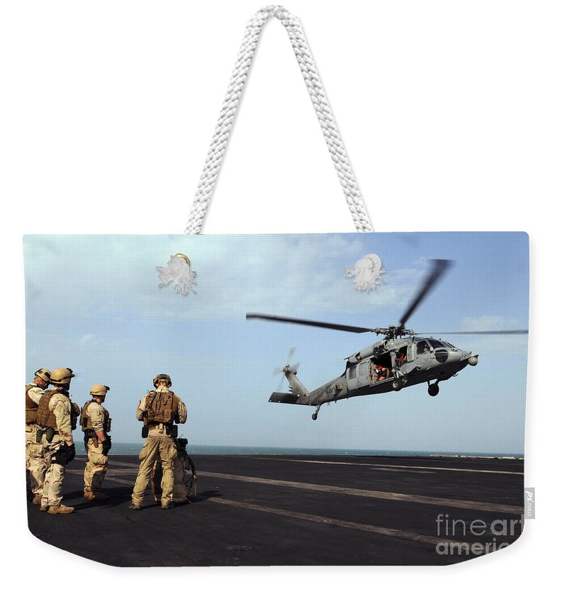 Aircraft Carrier Weekender Tote Bag featuring the photograph Sailors Prepare To Board An Mh-60s Sea by Stocktrek Images