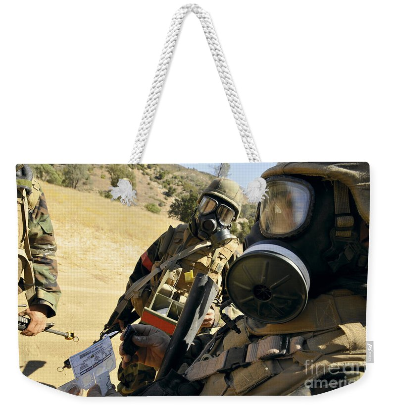 Naval Mobile Construction Battalion Weekender Tote Bag featuring the photograph Seabees Conduct Decontamination Wash by Stocktrek Images