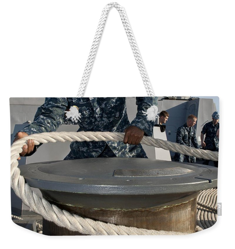 Military Weekender Tote Bag featuring the photograph Seaman Runs A Mooring Line by Stocktrek Images