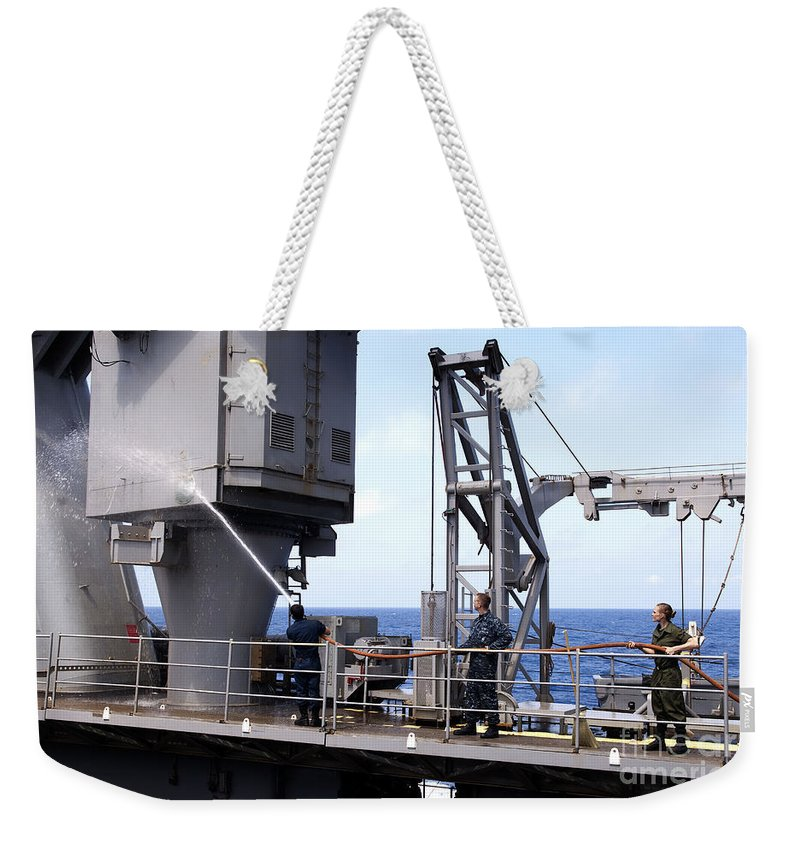 Maintenance Weekender Tote Bag featuring the photograph Seamen Conduct A Fresh Water Wash by Stocktrek Images