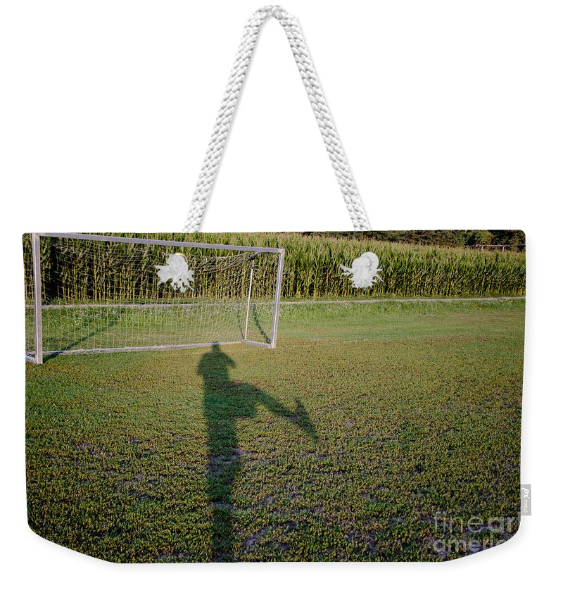 Football Weekender Tote Bag featuring the photograph Shadow From A Football Player by Mats Silvan