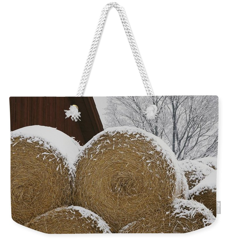 Natural Forces And Phenomena Weekender Tote Bag featuring the photograph Snow Dusts Rolls Of Hay by Mattias Klum