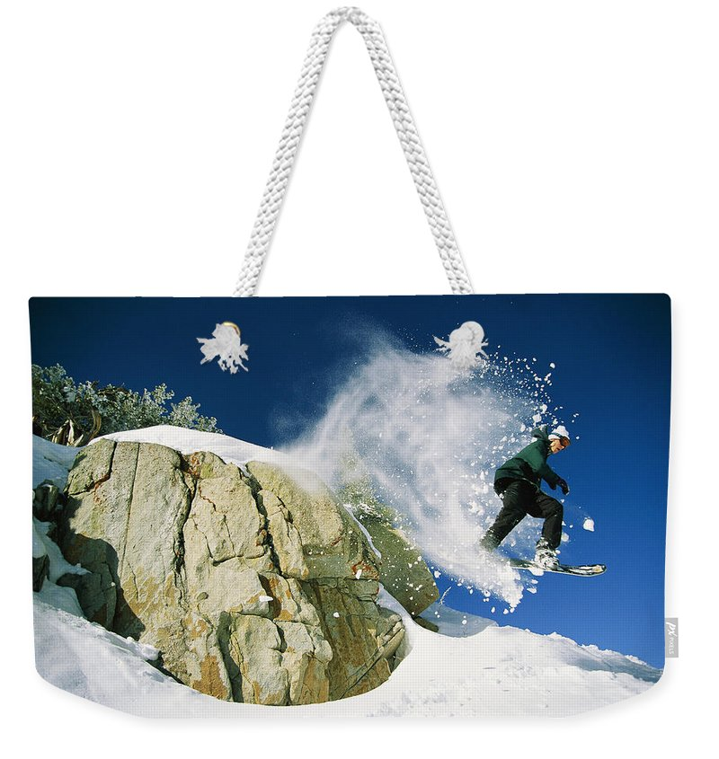 North America Weekender Tote Bag featuring the photograph Snowboarder Jumping Off A Big Rock by Skip Brown