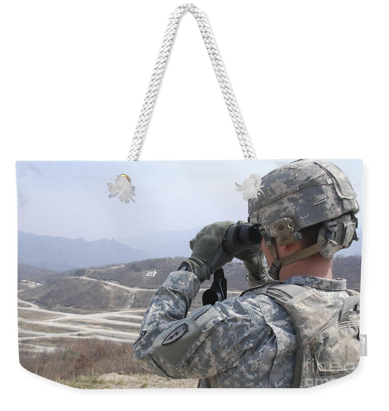 Military Weekender Tote Bag featuring the photograph Soldier Observes An Adjust Fire Mission by Stocktrek Images