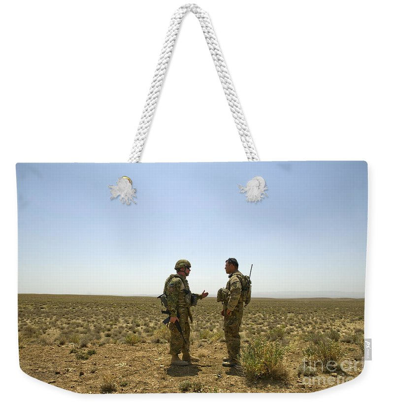 Afghanistan Weekender Tote Bag featuring the photograph Soldiers Discuss, Drop Zone by Stocktrek Images