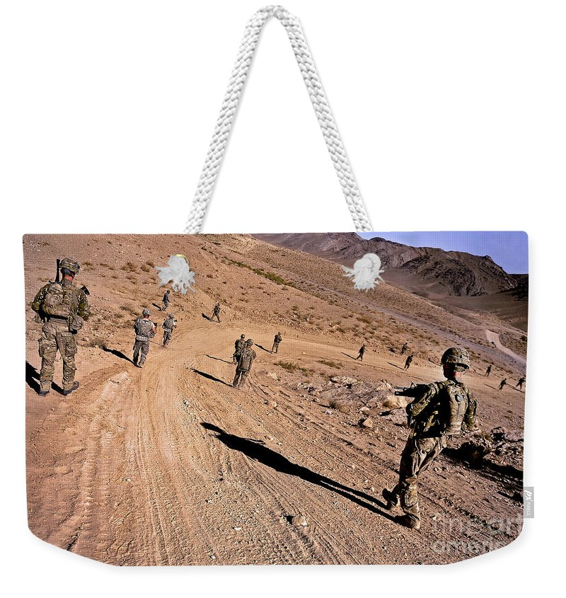 Provincial Reconstruction Team Weekender Tote Bag featuring the photograph Soldiers Patrol To A Village by Stocktrek Images